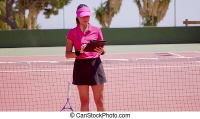 Woman with notebook and racket at tennis net - Attractive...