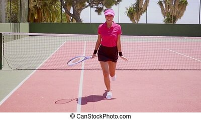 Excited young woman running across a tennis court - Excited...