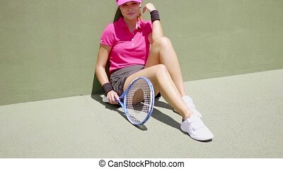 Woman seated with knees up leaning against wall of tennis...
