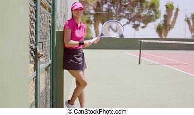 Woman with racket and tennis outfit poses against fence near...