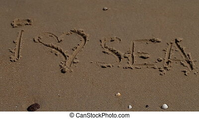 sea, shore, summer, vacation, love - inscription on sea sand...