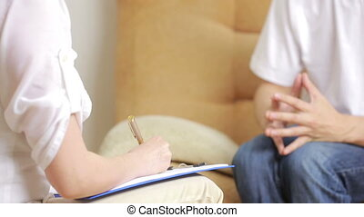 man talking with his therapist at therapy session - Young...