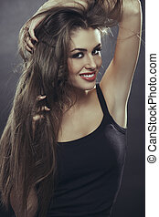 Happy lady with hands through long hair - Portrait of...