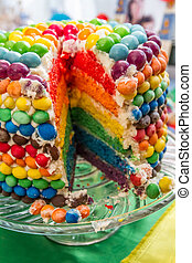 Rainbow birthday cake cutted on party table