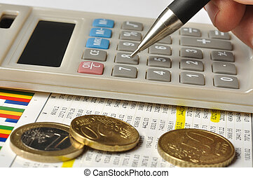 Calculations - Macro of calculator and euro coins, focus on...