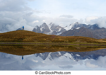 Tourist near a mountain lake - Man traveler stands on a...