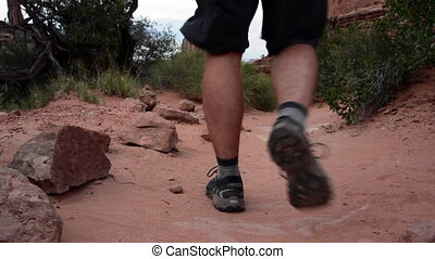 Arches Desert Trail Man Hikes Away - A man walks through the...