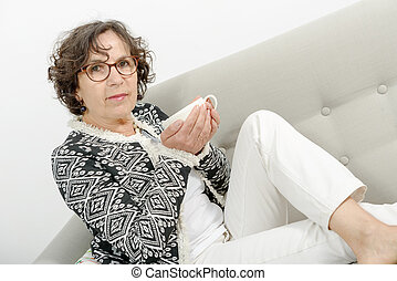 mature woman drinking tea on the sofa - beautiful mature...
