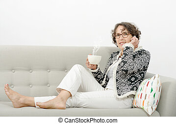 mature woman with phone, drinking tea on the sofa