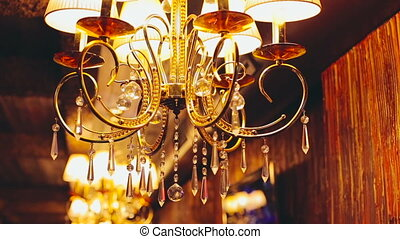 Gold chandelier with crystal balls shining, background