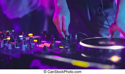DJ control desk, woman hand mixing, spinning in a Night Club...