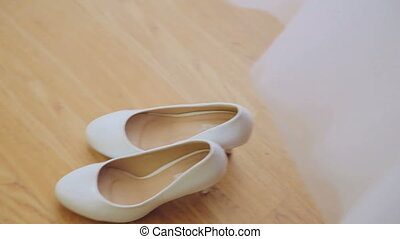 Brides wedding shoes decorated with rhinestones on the floor...