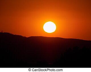 sunset - orange sunset against a hillside