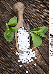 Stevia sweetener pills selective focus on wooden background...