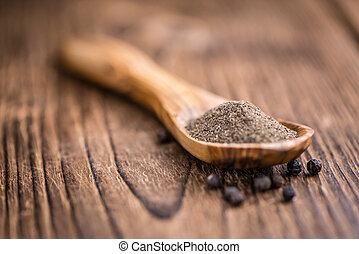 Black Pepper milled on vintage wooden background selective...
