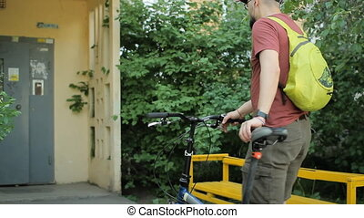 Man with smartphone and headphone on folding bicycle
