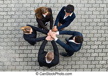 Businesspeople Stacking Hands - High Angle View Of...