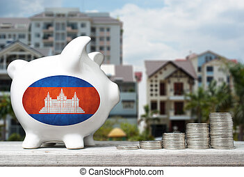 Cambodian real estate investment concept with piggy bank, stacks of coins and house in the background
