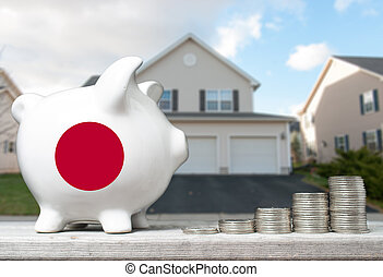 Japanese real estate investment concept with piggy bank, stacks of coins and house in the background