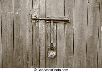 Old wooden gate with padlock in sepia