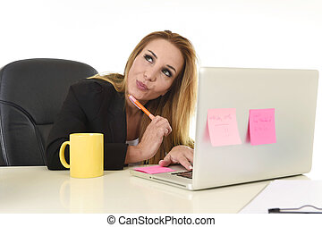 attractive 40s blond businesswoman working at office laptop...