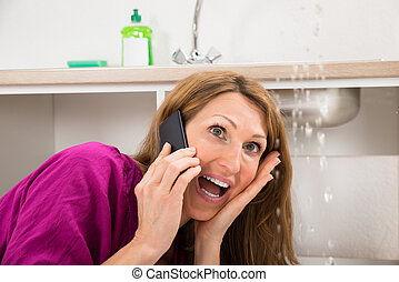 Close-up Of Woman Calling To Plumber While Water Leaking...