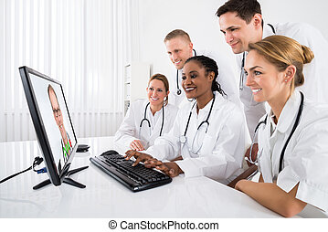 Doctors Videoconferencing On Computer - Group Of Doctors...