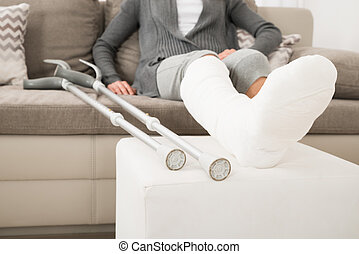 Woman With Plastered Leg Sitting On Couch - Close-up Of...