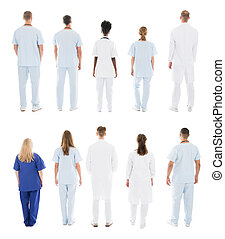 Rear View Of Medical Team Standing In Row Against White...