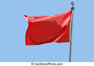Red Flag - Red flag flying in a stiff breeze against a clear...