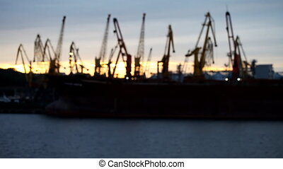 Silhouettes of cranes in the port on the river