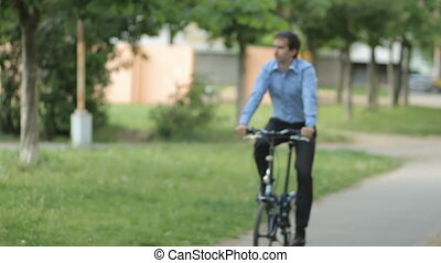 Businessman with little bicycle riding to the bench