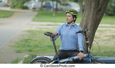 Businessman with little bicycle riding from the bench