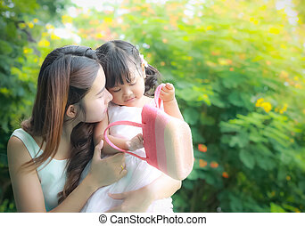 Asian mother take care young daugther in garden - close up...