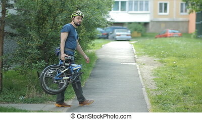 Man with beard folding bicycle near home