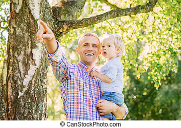 Young father with his son spending time in the park