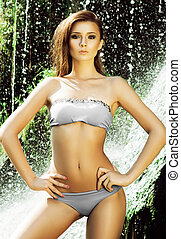 Young woman with a sporty body posing in a swimsuit.