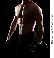 Strong, fit and sporty bodybuilder man with a dumbbell over...