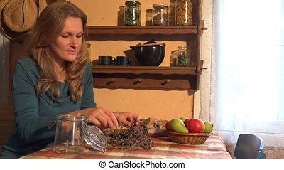 herbalist girl put oregano in glass. Ancient rural room. 4K...