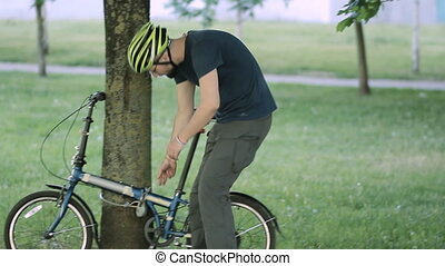 Man unlock the bicycle from a tree - A man with a beard...
