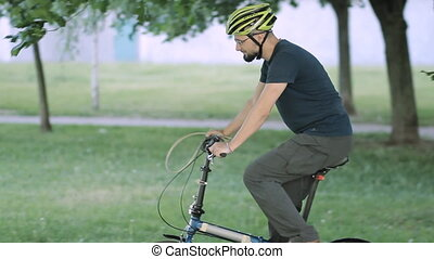 Man buckle the bicycle to a tree - A man with a beard...
