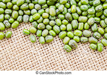 Mung bean seeds on sack background