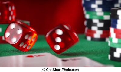Red dice in sequence rolls, casino chips, cards on green...