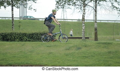 Man on bicycle riding to the park with loptop