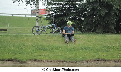 Man on bicycle and laptop riding from the park