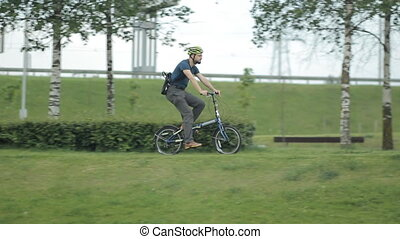 Man on bicycle riding to the park with tablet