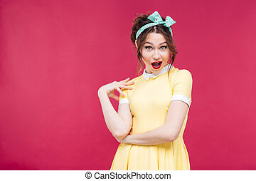 Amazed happy pinup girl in yellow dress standing and posing...