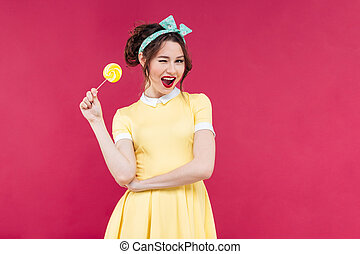 Cheerful charming pinup girl with yellow lollipop standing...