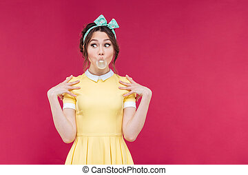 Cute playful pinup girl doing bubble with chewing gum over...