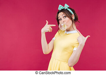Playful charming young woman pointing on bubble gum balloon
